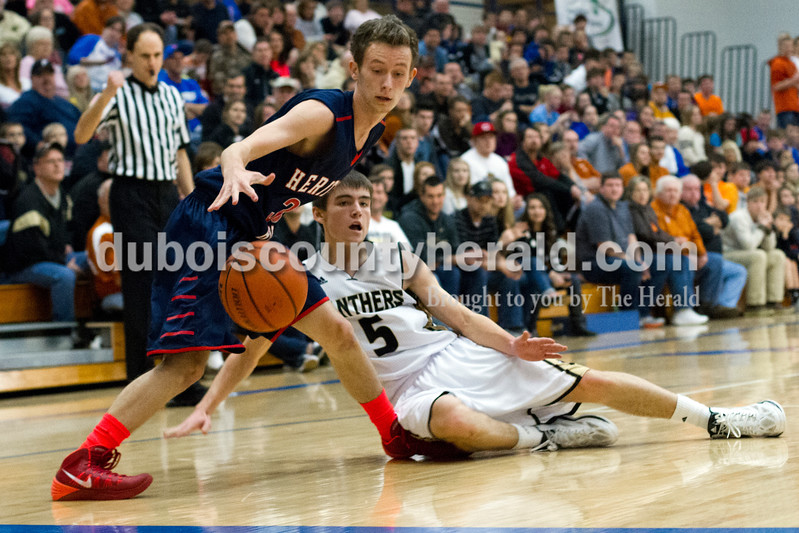 Heritage Hills' Justin Crane grabbed possession of the ball as it almost went out of bounds as Corydon Central's Timothy Wiseman fell during Monday night's PSC Holiday Classic championship in Reo. The Patriots lost 72-58. Ariana van den Akker/The Herald