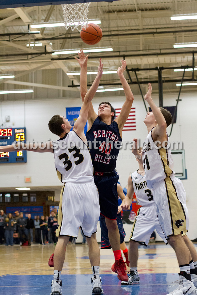 Heritage Hills' Devon Merder shot the ball over Corydon Central's Jay Brent, left, and Tyler Stauth during Monday night's PSC Holiday Classic championship in Reo. The Patriots lost 72-58. Ariana van den Akker/The Herald
