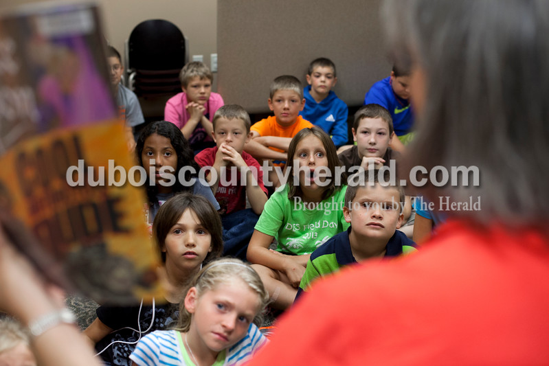 Chloe watched her interpreter, Kathy Buschkoetter, as librarian Anita Murphy read a book to Chloe's class during a field trip to Dubois Branch Library on Sept. 4. Ariana van den Akker/The Herald