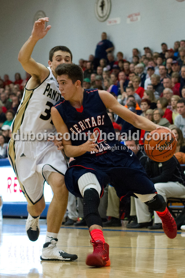 Heritage Hills' Gavin Schaefer dribbled the ball past Corydon Central's Mitchell Frederick during Monday night's PSC Holiday Classic championship in Reo. The Patriots lost 72-58. Ariana van den Akker/The Herald