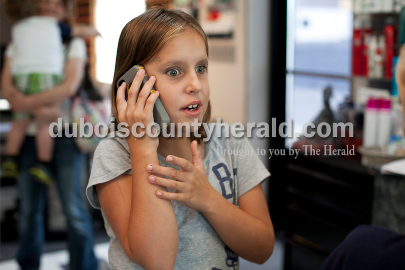 Chloe answered the phone for her paternal grandmother, Elaine Reuber of Dubois, while her grandmother had a hair appointment at Island Tropix in Jasper on Sept. 11. Though Chloe can't hear the person on the other end of the line, that doesn't stop her from answering the phone. Ariana van den Akker/The Herald