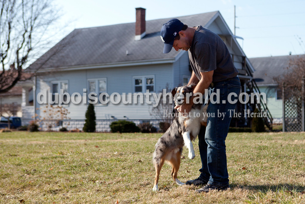 Ariana van den Akker/The Herald<br /> Jim Welp of Jasper paused to pet his 6-month-old Australian Shepherd Duke as he was talking him for a walk Sunday afternoon.  Welp was going to see relatives in Schnellville and wanted to make sure Duke got out before he went into his crate.