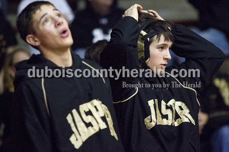 Jasper's Eric Gehlhausen, right, and Nathan Schitter reacted to a take down on teammate Tommy Brock during Saturday's wrestling sectional at Memorial Gym in Huntingburg. Rachel Mummey/The Herald