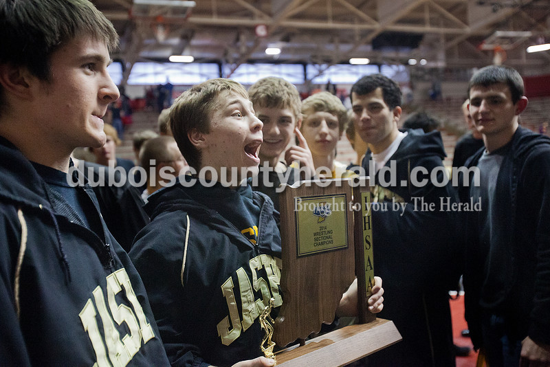 Jasper's Dillon Hurst, second from left, yelled out in celebration of taking first place at Saturday's wrestling sectional at Memorial Gym in Huntingburg. Rachel Mummey/The Herald
