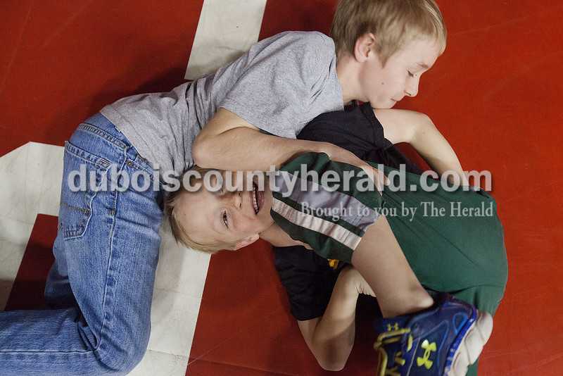 Elijah Brosmer of Ferdinand, 7, bottom, giggled as he play-wrestled with Patrick Recker of Ferdinand, 10, top, between rounds at Saturday's wrestling sectional at Memorial Gym in Huntingburg. Rachel Mummey/The Herald