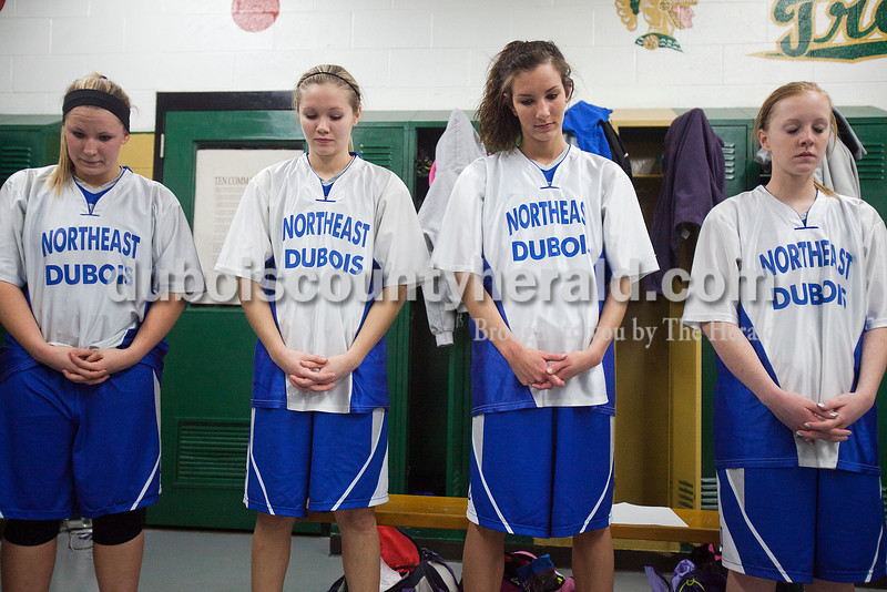 Northeast Dubois' Morgan Seng, Katelyn Helming, Rachel Breitwieser and Chloe Johnson prayed before the start of Saturday's Class 1A sectional championship against Wood Memorial in Oakland City. Northeast Dubois lost in overtime 62-57. Rachel Mummey/The Herald