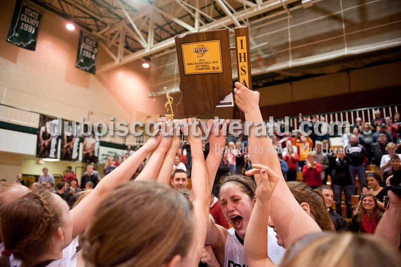 Carolyn Van Houten/The Herald<br /> The Southridge Raiders hoisted their trophy up after winning the Class 3A girls basketball sectional championship at Alice Arena in Vincennes on Saturday.  Southridge defeated Vincennes 46-41.