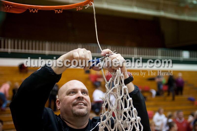 Carolyn Van Houten/The Herald<br /> Southridge's Head Coach Greg Werner cut down the net after the Raiders won the Class 3A girls basketball sectional championship at Alice Arena in Vincennes on Saturday.  Southridge defeated Vincennes 46-41.