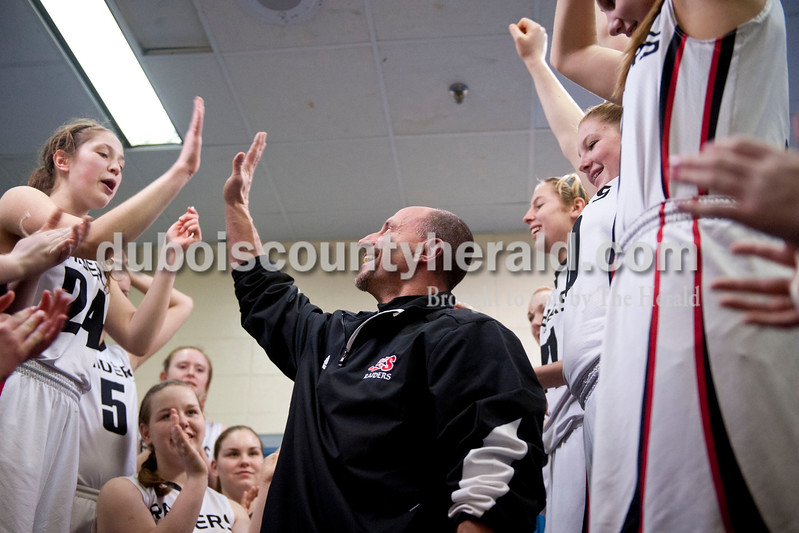 Carolyn Van Houten/The Herald<br /> Southridge's Coach Tim Underhill gave Sydney Altmeyer a high-five once he did eighty push-ups after the Raiders won the Class 3A girls basketball sectional championship at Alice Arena in Vincennes on Saturday.  Southridge defeated Vincennes 46-41.  Head Coach Greg Werner told his team that he would do double the push-ups for every point scored during the championship as well as a push-up for every point scored in the semi-final, which he calculated to be about 150 push-ups.  Coach Tim Underhill helped Werner with the remaining push-ups when Werner finished seventy of them.
