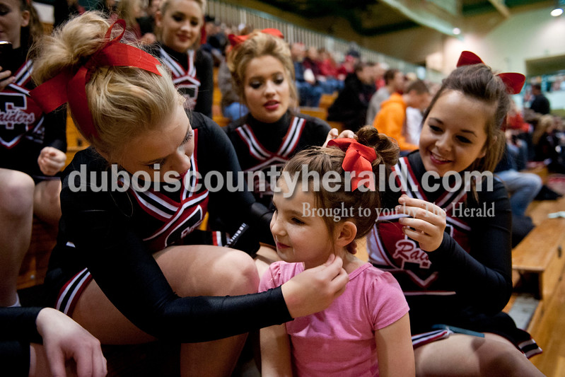 Carolyn Van Houten/The Herald<br /> Southridge cheerleaders Jessica Lubbehusen, junior, left, Skylar Kemp, sophomore, and Kaylyn Long, senior, helped Ellie Bardwell of Huntingburg, 7, with her hair before the Class 3A girls basketball sectional championship at Alice Arena in Vincennes on Saturday.  Southridge defeated Vincennes 46-41.
