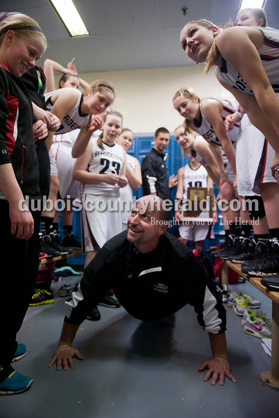 """Carolyn Van Houten/The Herald<br /> Southridge's Coach Tim Underhill looked up to ask, """"Am I done yet?"""" while he did eighty push-ups after the Raiders won the Class 3A girls basketball sectional championship at Alice Arena in Vincennes on Saturday.  Southridge defeated Vincennes 46-41.  Head Coach Greg Werner told his team that he would do double the push-ups for every point scored during the championship as well as a push-up for every point scored in the semi-final, which he calculated to be about 150 push-ups.  Underhill helped Werner with the remaining push-ups when Werner finished seventy of them."""