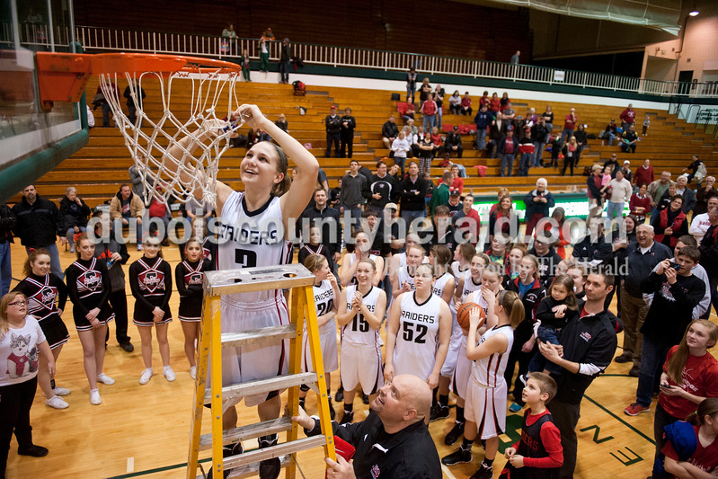 Carolyn Van Houten/The Herald<br /> Southridge's Kayla Voegerl cut down the net after the Raiders won the Class 3A girls basketball sectional championship at Alice Arena in Vincennes on Saturday.  Southridge defeated Vincennes 46-41.