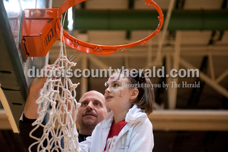 Carolyn Van Houten/The Herald<br /> Southridge Coach Tim Underhill helped Gabbie Werner of Huntingburg, 10, cut down the net after the Raiders won the Class 3A girls basketball sectional championship at Alice Arena in Vincennes on Saturday.  Gabbie is Southridge's Head Coach Greg Werner's daughter.  Southridge defeated Vincennes 46-41.