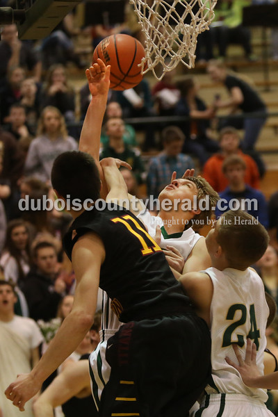 Heather Rousseau/The Herald<br /> Forest Park's Damon Wilmes went up for a shot with teammate,  Ben Wendholt. right, and Gibson Southern's Reed Farmer on defense during Tuesday night's game in Ferdinand. The Rangers won 56-36.