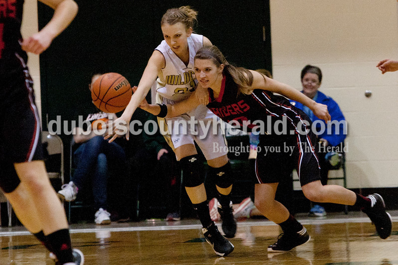 Heather Rousseau/The Herald<br /> Jasper's Maddison Ubelhor, left, and Southridge's Aubrey Main fought for the ball during Wednesday night's class 3A girls basketball sectional at Alice Arena in Vincennes. The Raiders won 48-44.