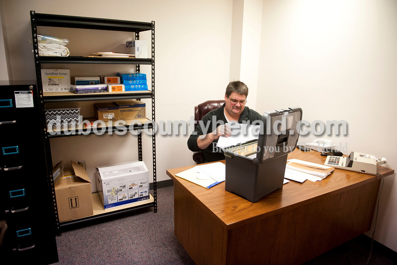 Carolyn Van Houten/The Herald<br /> Bob Veatch, the Dubois County coroner, worked on paperwork in his new office in the County Courthouse Annex on Friday.  Before he moved into his office this week, he had to store autopsy records at his home.