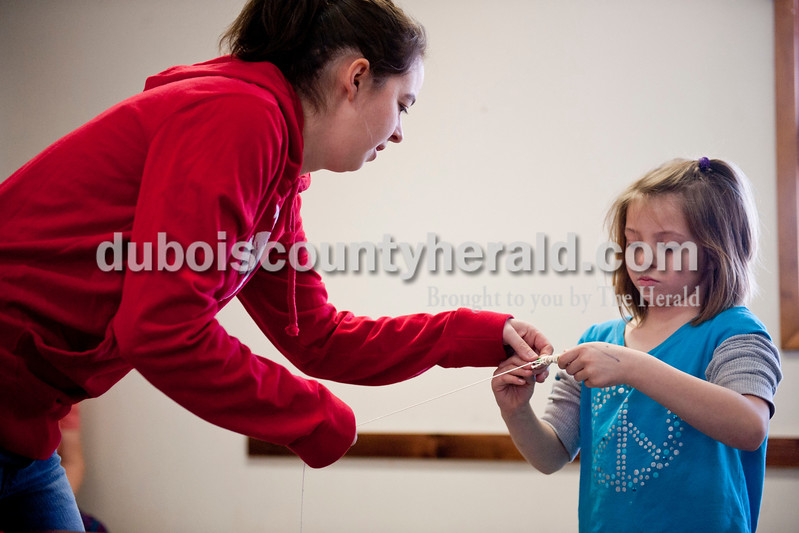 Carolyn Van Houten/The Herald<br /> Crissy Casper of Birdseye, left, helped her niece Kendall King, 7, of St. Meinrad, wrap string for her kite around a popsicle stick during the Fly A Kite Workshop held in the Newton Stewart State Recreation Area in Wickliffe on Saturday.  Children built kites using patterns and materials provided by the Patoka Lake Visitor Center.  After building the kites, the children and their families went to the park's beach to fly the kites.