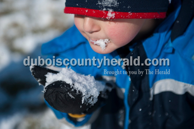 "Carolyn Van Houten/The Herald<br /> Holden Bastien, 4, ate a snowball outside of his home in Jasper on Tuesday.  ""We like to play in the snow a lot, but we don't always get to play in it so this is fun,"" his brother Alex Bastien, 7, said.  ""The wind makes it really cold though."""
