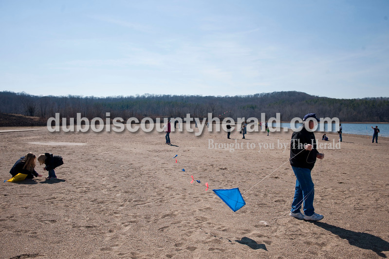 Carolyn Van Houten/The Herald<br /> Ella Jones, 7, left, played in the sand with her cousin Drew Estabrook, 4, both of Jasper, while Steve Chambers of Holland, right, walked with the kite he and his granddaughter made together during the Fly A Kite Workshop held in the Newton Stewart State Recreation Area in Wickliffe on Saturday.  Children built kites using patterns and materials provided by the Patoka Lake Visitor Center.  After building the kites, the children and their families went to the park's beach to fly the kites.