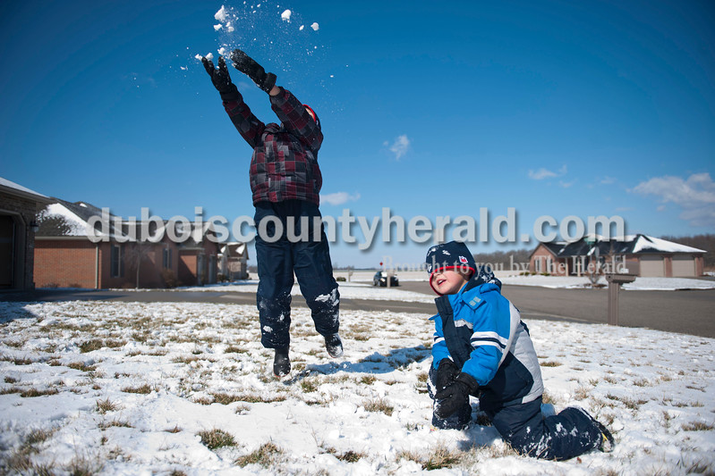 "Carolyn Van Houten/The Herald<br /> Alex Bastien, 7, left, jumped and smashed a snowball next to his brother Holden Bastien, 4, outside of their home in Jasper on Tuesday.  ""We like to play in the snow a lot, but we don't always get to play in it so this is fun,"" Alex said.  ""The wind makes it really cold though."""
