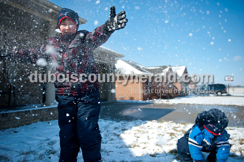 "Carolyn Van Houten/The Herald<br /> Alex Bastien, 7, left, smashed a snowball next to his brother Holden Bastien, 4, outside of their home in Jasper on Tuesday.  ""We like to play in the snow a lot, but we don't always get to play in it so this is fun,"" Alex said.  ""The wind makes it really cold though."""