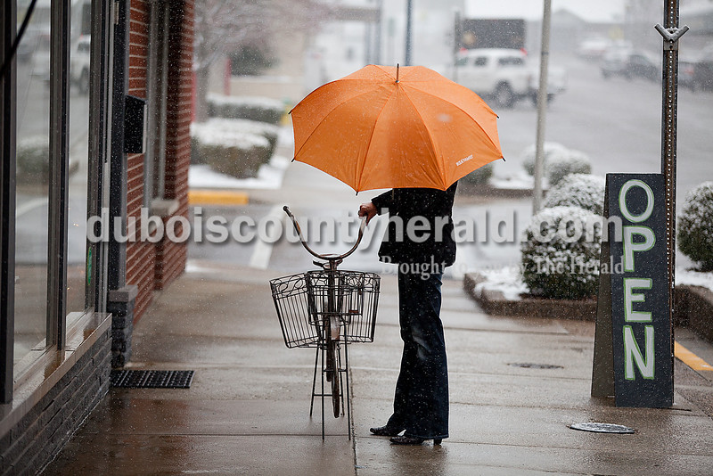 Rachel Mummey/The Herald<br /> Angela Hildenbrand of Jasper placed a decorative bicycle outside of Elements of Design as she opened the store for regular business hours Tuesday morning in Jasper. Hildenbrand said she doesn't think the weather will influence business.