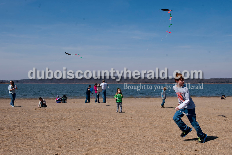 Carolyn Van Houten/The Herald<br /> Ruby Carter of Pekin, 4, center, flew a kite for the first time while Rylan Morrison of Princeton, 10, right, ran down the beach trying get his kite up in the air during the Fly A Kite Workshop held in the Newton Stewart State Recreation Area in Wickliffe on Saturday.  Children built kites using patterns and materials provided by the Patoka Lake Visitor Center.  After building the kites, the children and their families went to the park's beach to fly the kites.