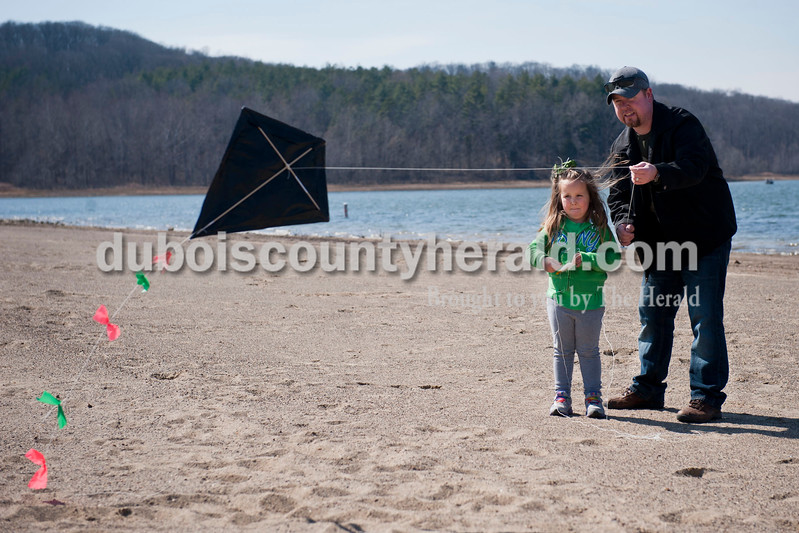Carolyn Van Houten/The Herald<br /> Ruby Carter of Pekin, 4, flew a kite for the first time with her father James Carter during the Fly A Kite Workshop held in the Newton Stewart State Recreation Area in Wickliffe on Saturday.  Children built kites using patterns and materials provided by the Patoka Lake Visitor Center.  After building the kites, the children and their families went to the park's beach to fly the kites.