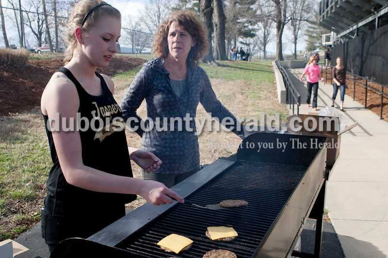 Heather Rousseau/The Herald<br /> Jasper sophomore Haley Sample and Caroline Gobert, grilled burgers to be sold at the concession stand during Monday night's baseball game against New Trier in Jasper. Caroline is married to Jasper's coach Terry Gobert and helps out where she can.
