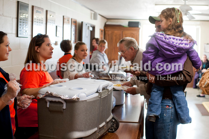 "Carolyn Van Houten/The Herald<br /> Firefighter Clint Eichmiller, right, held his daughter Laken, 3, while getting food during the benefit breakfast for his family at the Dubois Volunteer Fire Department in Dubois on Sunday morning.  The Eichmillers lost their entire home and all of their possessions in a fire on February 28, 2014.  Over 400 people came to the benefit breakfast to support the family.  ""The turnout this morning is really overwhelming,"" Eichmiller said."