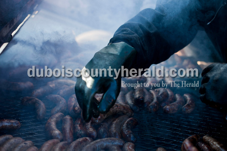 "Carolyn Van Houten/The Herald<br /> Firefighter Cory Voegerl of Dubois grilled sausages during the benefit breakfast for Firefighter Clint Eichmiller and his family at the Dubois Volunteer Fire Department on Sunday morning.  The Eichmillers lost their entire home and all of their possessions in a fire on February 28, 2014.  Over 400 people came to the benefit breakfast to support the family.  ""The turnout this morning is really overwhelming,"" Clint Eichmiller said."