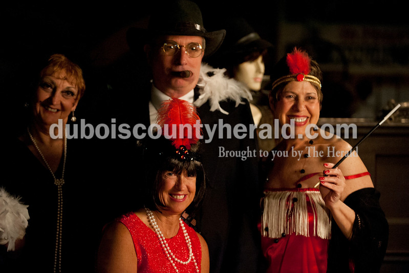 "Carolyn Van Houten/The Herald<br /> Ruth Kuebler of Jasper, left, Gary Eck, upper center, his wife Marlene Eck, lower center, both of Otwell, and Yvonne Mullen of Jasper stood for a picture together after winning ""Best Costumes"" during the ""Party like it's 1929!"" event at the Dubois County Museum in Jasper on Saturday.  They each were awarded museum memberships.  The evening event was themed around the prohibition days, featuring a moonshine demonstration, costume contest, and live music by the Recycled Teenagers."