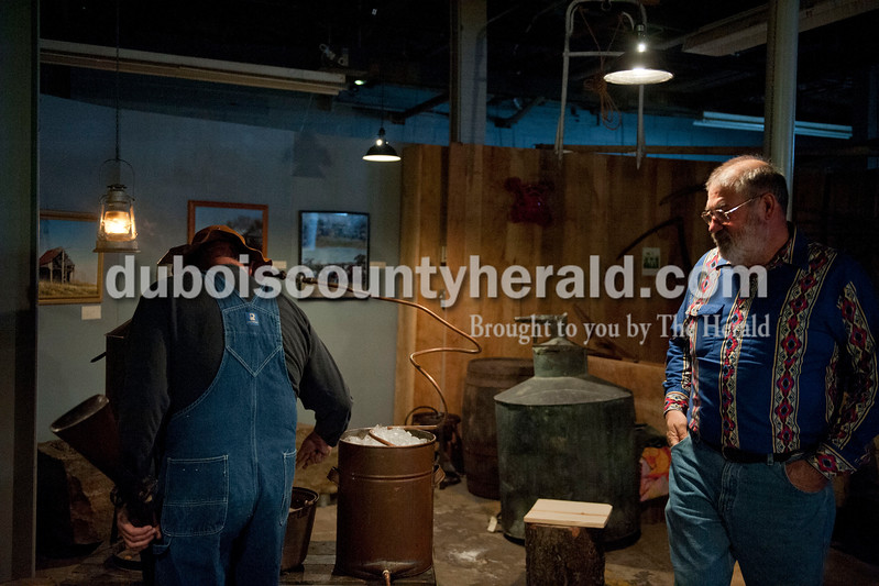 "Carolyn Van Houten/The Herald<br /> Paul Schue of Huntingburg, right, watched as Mike Lindauer of Ferdinand checked on his family's distilling equipment which was on display during the ""Party like it's 1929!"" event at the Dubois County Museum in Jasper on Saturday.  The evening event was themed around the prohibition days, featuring a moonshine demonstration, costume contest, and live music by the Recycled Teenagers."