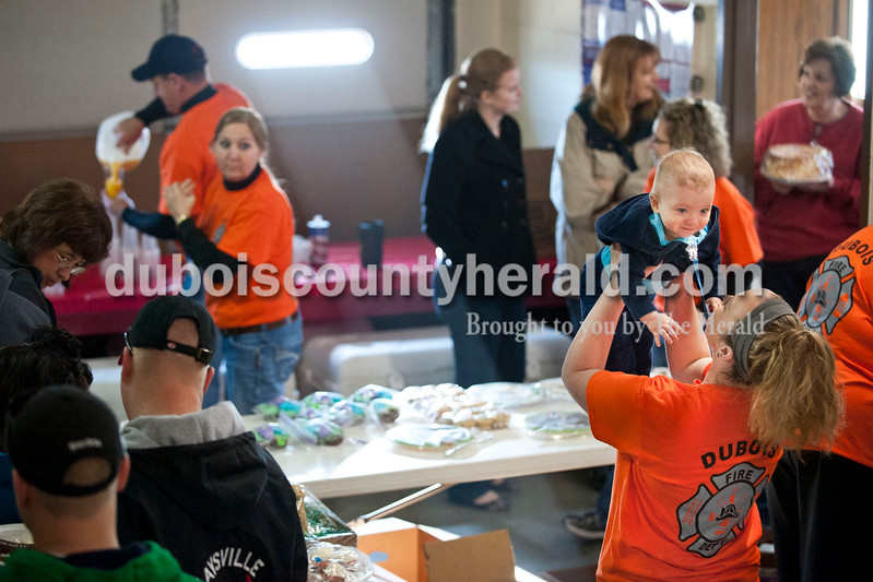 "Carolyn Van Houten/The Herald<br /> Cassie Miller, right, lifted her one-year-old son Blake, both of Jasper, into the air while working the bake sale during the benefit breakfast for Firefighter Clint Eichmiller and his family at the Dubois Volunteer Fire Department in Dubois on Sunday morning.  The Eichmillers lost their entire home and all of their possessions in a fire on February 28, 2014.  Over 400 people came to the benefit breakfast to support the family.  ""The turnout this morning is really overwhelming,"" Clint Eichmiller said.  Miller's father is a volunteer firefighter who works with Eichmiller."