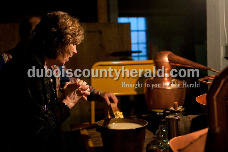 "Carolyn Van Houten/The Herald<br /> Joan Melton of Celestine looked at the corn maize mash, which is a part of the process of making moonshine, during the ""Party like it's 1929!"" event at the Dubois County Museum in Jasper on Saturday.  The evening event was themed around the prohibition days, featuring a moonshine demonstration, costume contest, and live music by the Recycled Teenagers."