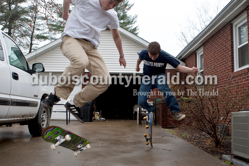 "Heather Rousseau/The Herald<br /> Christian Leinenbach of Jasper, left and Grant Brescher of Ireland, both 18, practiced kick flips on their skateboards at Leinenbac's home on Monday. The two want to get better at skating because they plan to attend Indiana State University next year, ""we will need some kind of transportation between classes,"" said Leinenbach. Brescher  said he just started skateboarding about two weeks ago and  Leinenbach started at the age of 10, but stopped skating for a while and picked it up again recently."