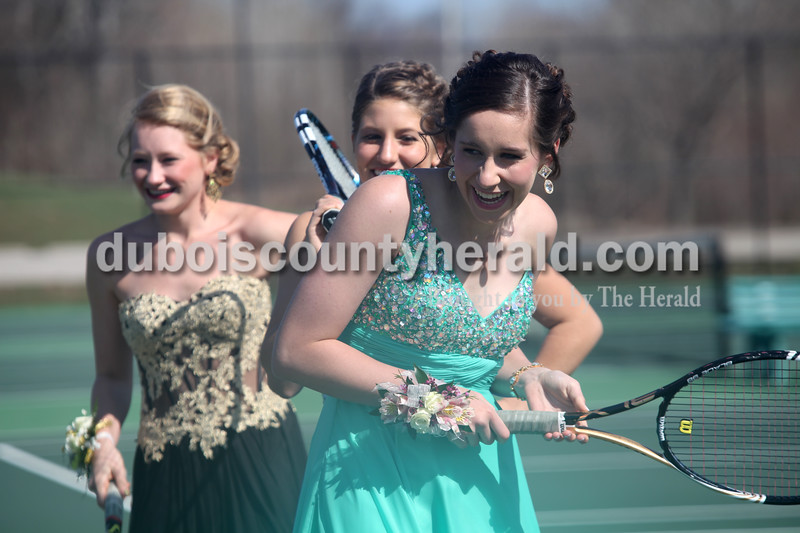 Heather Rousseau/The Herald<br /> Jasper High School juniors, Elisabeth Ahlbrand, right, Anna Flick, and Julia Ariens, left, smiled as their tennis teammates came to join them on the Jasper tennis courts for group pictures before prom on Saturday. The Jasper girls tennis team have had this tradition since 1998 and a picture from each year is displayed with their sectional championship trophies.