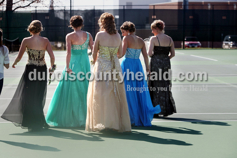 Heather Rousseau/The Herald<br /> Jasper High School juniors, from left, Julia Ariens, Elisabeth Ahlbrand, Livia Heller, Anna Flick, and Claire Egler walked across the Jasper tennis courts for group pictures before prom on Saturday. The Jasper girls tennis team have had this tradition since 1998 and a picture from each year is displayed with their sectional championship trophies.
