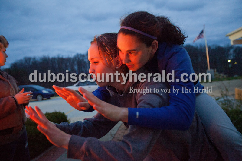 Rachel Mummey/The Herald<br /> Sara Mehringer of Dubois, 17, and Brynn Hoffman of Haysville, 17, warmed her hands by a trashcan fire at St. Celestine Church in Celestine on Friday. Youth from the parish built a shanti town out of cardboard boxes and slept in them overnight to experience and learn about homelessness.