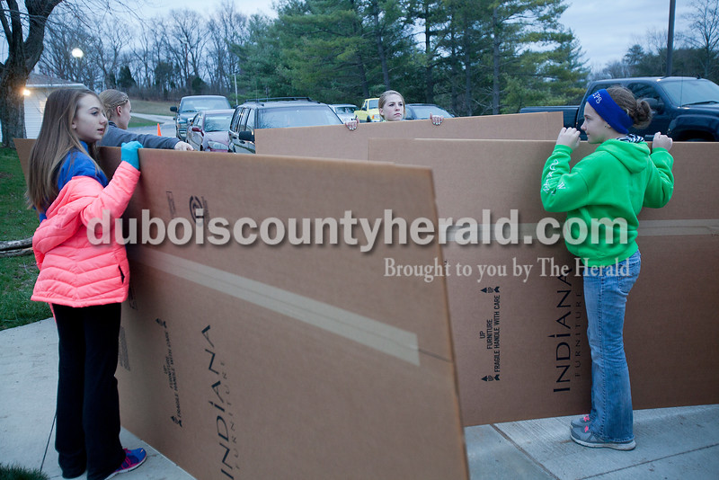 Rachel Mummey/The Herald<br /> Elizabeth Kunz of Celestine, 13, left, Madelyn Pund of Bretzville, Clare Mangin of Dubois, 14, and Mara Schroering of Celestine, 14, received their cardboard boxes at St. Celestine Church in Celestine on Friday. Youth from the parish built a shanti town out of cardboard boxes and slept in them overnight to experience and learn about homelessness.