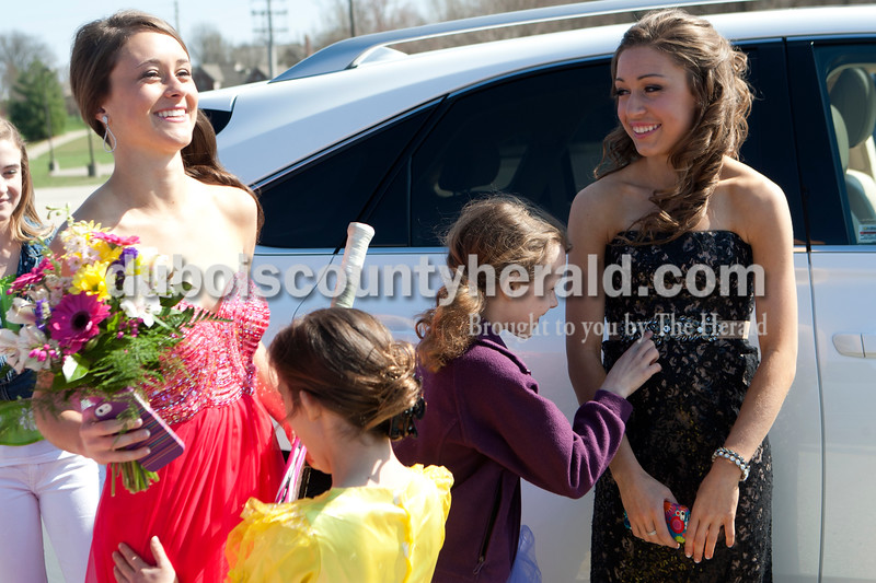 Heather Rousseau/The Herald<br /> Valerie Sargent, left and Emily Messmer, right, both seniors on the Jasper High School tennis team, smiled as Mariand Hays, 7, left and her sister, Lauren, 9, both daughters of the junior varsity coach Jeff Hayes, admired their prom dresses on Saturday outside the tennis courts before prom. The tennis team has had a tradition since 1998 to meet for group pictures before prom. A picture from each year is displayed with their sectional championship trophies.