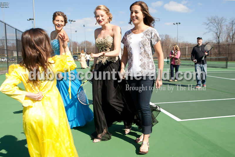 Heather Rousseau/The Herald<br /> Jasper High School tennis team members, Anna Flick, left, and Julia Ariens, both juniors, and Emma Seger, a sophomore, chatted with Mariand Hays, 7, the daughter of junior variety coach Jeff Hayes, back right, on Saturday before prom. They were on the high school tennis courts after having a group photo taken. It has been a tradition for the tennis team since 1998 to have a picture taken together in their prom dresses at the tennis courts. The photos are on display with the sectional championship trophies they have won consecutively every year.