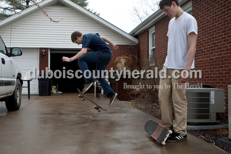"Heather Rousseau/The Herald<br /> Grant Brescher of Ireland, left and Christian Leinenbach of Jasper, both 18, practiced kick flips on their skateboards at Leinenbac's home on Monday. The two want to get better at skating because they plan to attend Indiana State University next year, ""we will need some kind of transportation between classes,"" said Leinenbach. Brescher  said he just started skateboarding about two weeks ago and  Leinenbach started at the age of 10, but stopped skating for a while and picked it up again recently."
