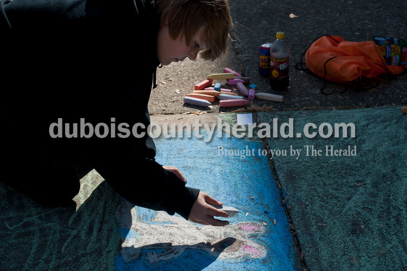 Carolyn Van Houten/The Herald<br /> Aidan Uebelhor of Jasper, 10, drew a rabbit during the 11th Annual Chalk Walk Arts Festival in Jasper on Saturday.  The event, which is put on by the Jasper Community Arts Commission, transforms the sidewalks on the Square into huge murals made with colorful chalk.