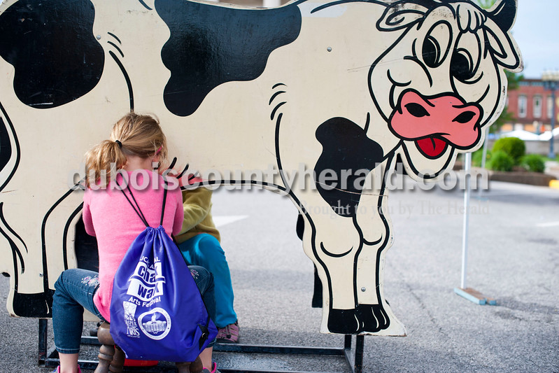 Carolyn Van Houten/The Herald<br /> Chloe Tooley of Huntingburg, 7, raced to milk colored water from a wooden cow during the 11th Annual Chalk Walk Arts Festival in Jasper on Saturday.  The event, which is put on by the Jasper Community Arts Commission, transforms the sidewalks on the Square into huge murals made with colorful chalk.