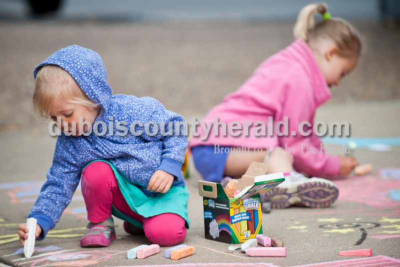 Carolyn Van Houten/The Herald<br /> Addyson Dimmick, 2, left, and her sister Mya Dimmick, 5, both of Jasper, drew pictures of castles, unicorns and cats during the 11th Annual Chalk Walk Arts Festival in Jasper on Saturday.  The event, which is put on by the Jasper Community Arts Commission, transforms the sidewalks on the Square into huge murals made with colorful chalk.