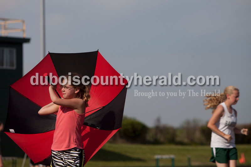 Ella Thompson, 8, of Huntingburg held an umbrella to try and block the sun during  the track meet at Forest Park in Ferdinand against Southridge on Monday. The Raiders girls won 67-65 and Rangers boys won 81-51. Heather Rousseau/The Herald