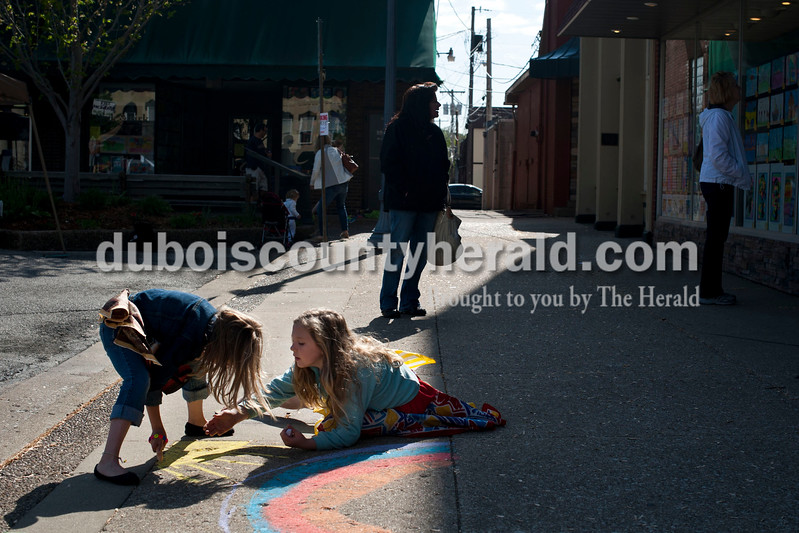 Carolyn Van Houten/The Herald<br /> Avery Fuhs, left, and Ella Jones, both 7 and of Jasper, drew a sun together during the 11th Annual Chalk Walk Arts Festival in Jasper on Saturday.  The event, which is put on by the Jasper Community Arts Commission, transforms the sidewalks on the Square into huge murals made with colorful chalk.