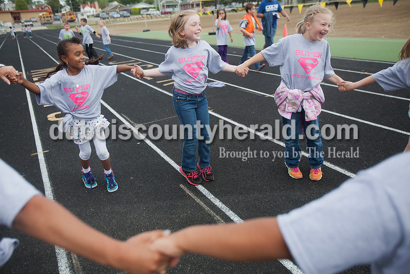 Rachel Mummey/The Herald<br /> First-graders Cara Jones, left, Ali Werner, and kindergartner Mackenzie Walsh joined hands while dancing during Fifth Street Elementary School's fourth annual Whiskers Walk at Jerry Brewer Alumni Stadium on Friday. The event encouraged kids in all grades to walk for thirty minutes to raise awareness of childhood obesity and promote health and wellness.