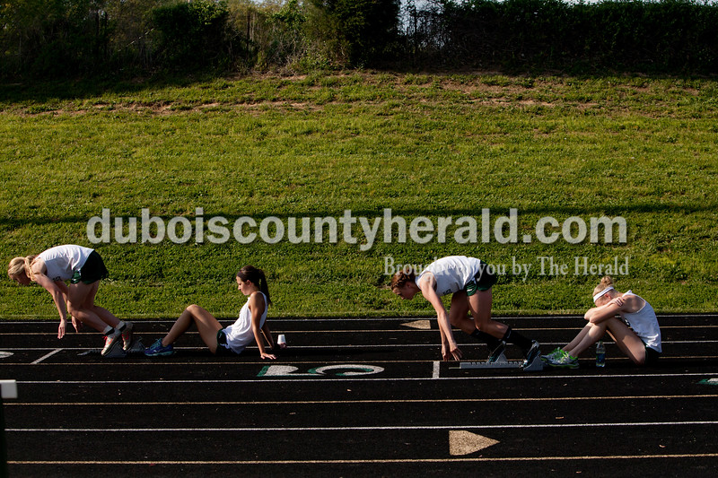 Forest Park's Tori Lange, left, and Madisyn Hunt got into starting position before the 200-meter run as their teammates  held the blocks during the track meet in Ferdinand on Monday.  The Raiders girls won 67-65 and Rangers boys won 81-51. Heather Rousseau/The Herald